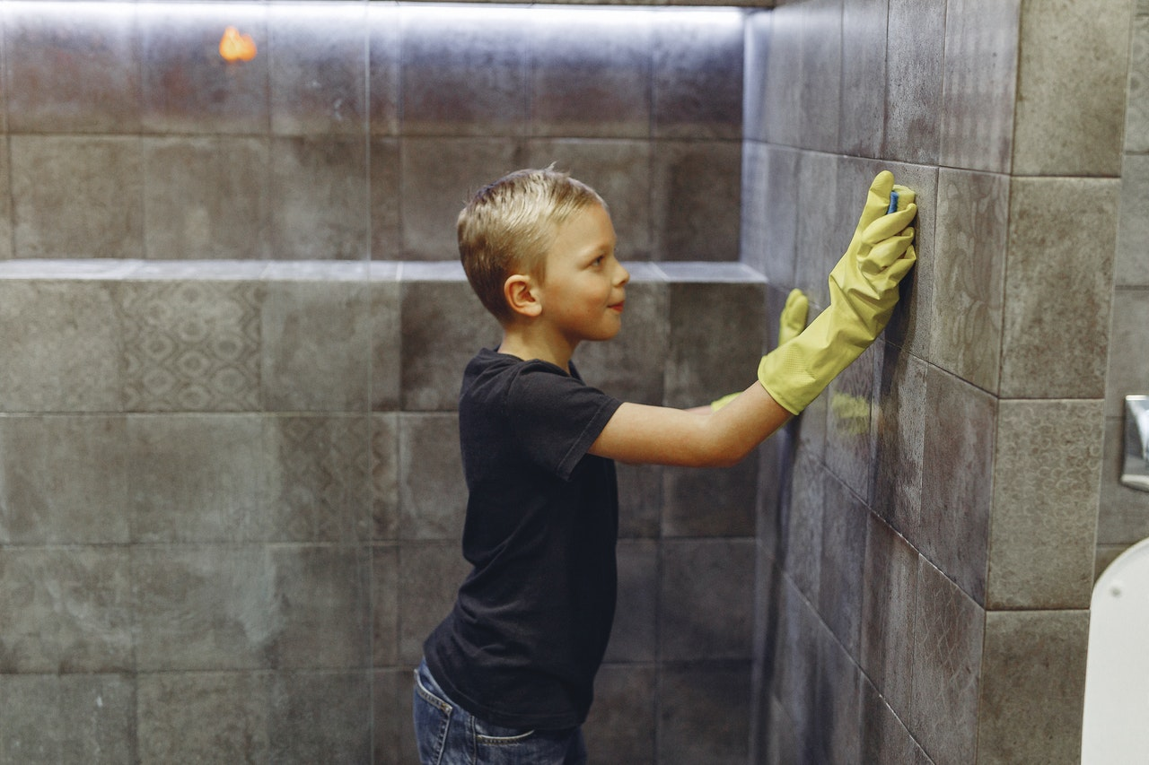 A boy cleans shower walls and time management experts encourage parents to get children to help with the house