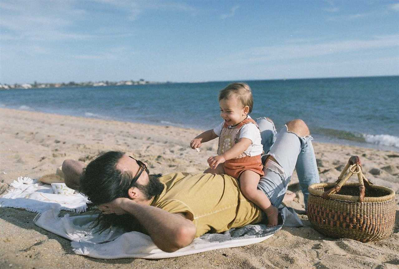Husband and baby daughter sit on top of him while they are on the beach for a story about where new dads can find support.