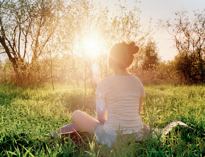 Young woman is sitting in yoga position and enjoying the sunset in nature